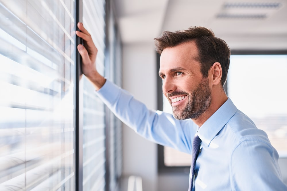 Smiling businessman looking out of office window - Igniyte